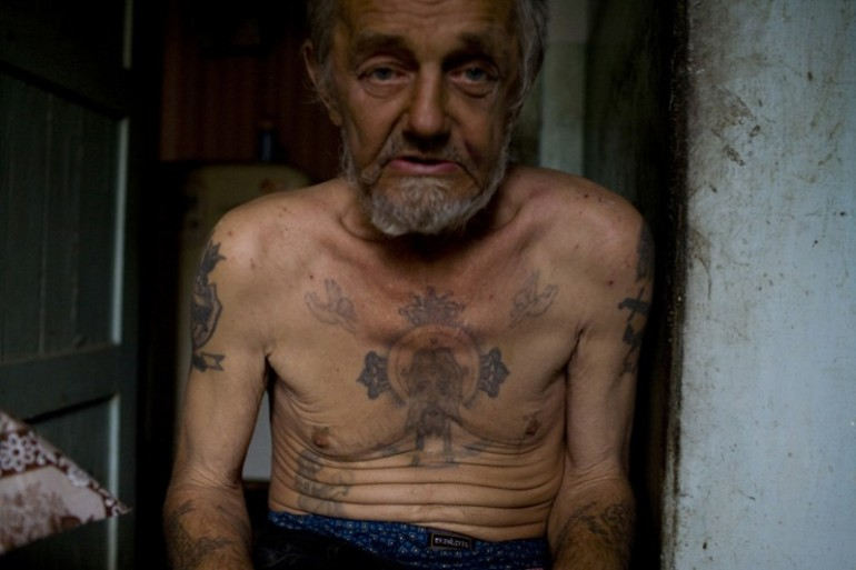 Old and tired Russian criminal with tattoos.