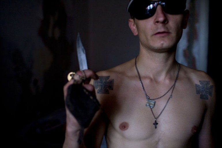 Criminal with prisoner tattoos and knife.